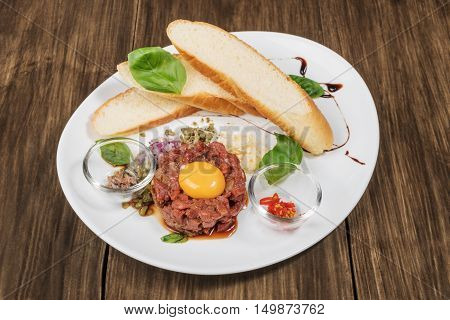 Beef tartare with parmesan cheese raw egg and a small toast served on a plate on old wooden table
