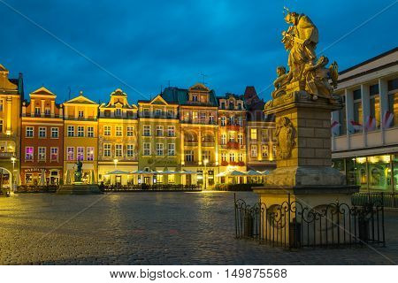 Poznan Poland - September 30 2016: Night photo of Poznan Old Town with Saint John of Nepomuk statue and numerous of illuminated townhouses.