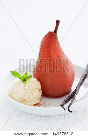 Homemade poached pear with vanilla ice cream mint and vanilla sticks closeup