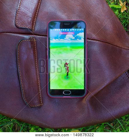 Dnipro, Ukraine - July 23, 2016: The hit augmented reality smartphone app Pokemon GO shows a Pokemon encounter overlain in park in the real world.