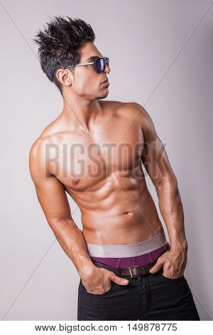 Shirtless attractive middle eastern fashion model muscular guy in black jeans standing on podium on grey background.