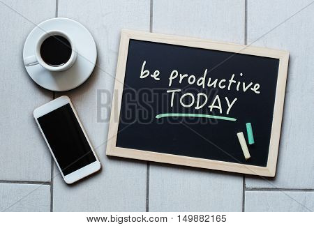 Chalkboard or Blackboard concept saying Be Productive Today with coffee and mobile phone. Business Education Effective Management concept.