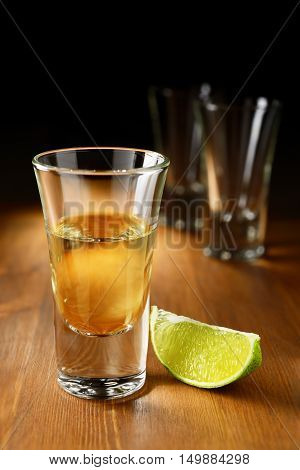 Gold tequila shot with lime on the wood bar counter