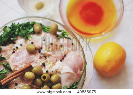 On the table in a glass dish the pieces of raw chicken in the marinade decorated with olives parsley cinnamon and lemon