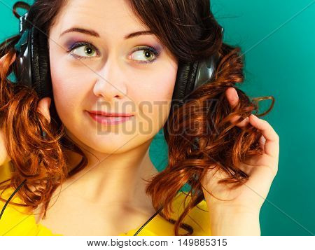 Young people leisure relax concept. Closeup teen cute girl in big headphones listening music mp3 relaxing on green blue background