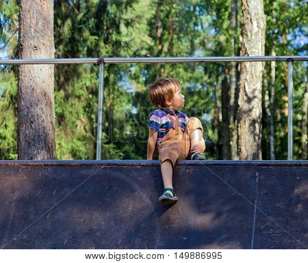 cool little boy sitting on ramp for extreme bicycle riding