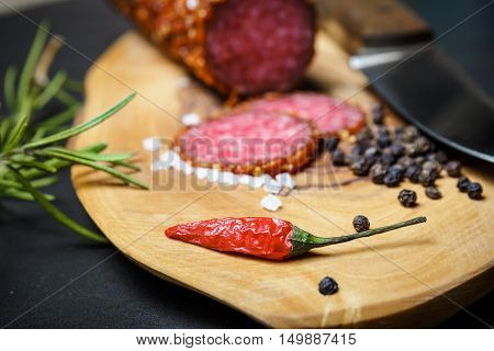 Dried Salami Crusted In Ground Red Pepper On Dark Background