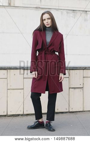 young stylish woman in classic red trench coat melange blouse and black shoes - street fashion
