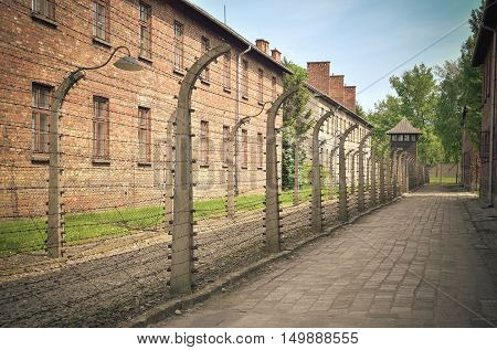 OSWIECIM POLAND - MAY 12 2016: Masonry block and fence with barbed wire in concentration camp Auschwitz-Birkenau in Oswiecim Poland.