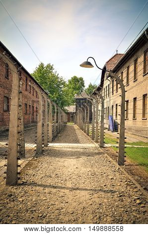 OSWIECIM POLAND - MAY 12 2016: Masonry blocks and fences with barbed wire in concentration camp Auschwitz-Birkenau in Oswiecim Poland.