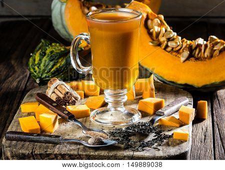 Pumpkin tea. Cup of autumm hot drink - pumpkin tea with ingredients - pumpkin, tea, cinnamon, nutmeg. Wooden rustic background