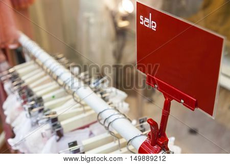 A red sale sign on rail of clothes in a shop