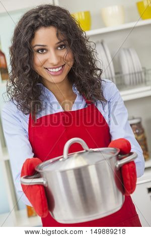 A beautiful Latina girl or young woman looking happy wearing red apron, cooking holding metal pot in her kitchen at home