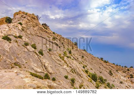 The ancient walls of Genoese Sudak Castle mountain and storm clouds during sunset in Crimea Sudak. Scenic views of rocky cliffs near ancient Genoese fortress
