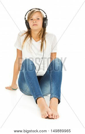 Young girl sitting on the floor listening to music with headphones over white background
