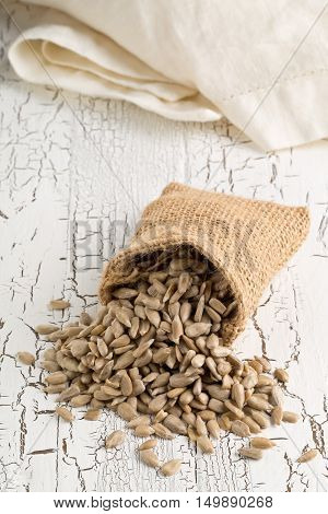 Natural shelled sunflower seeds in burlap sack on rustic white table