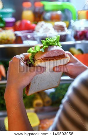 Hungry Woman holding a sandwich in his hands and standing next to the open fridge. Unhealthy food.