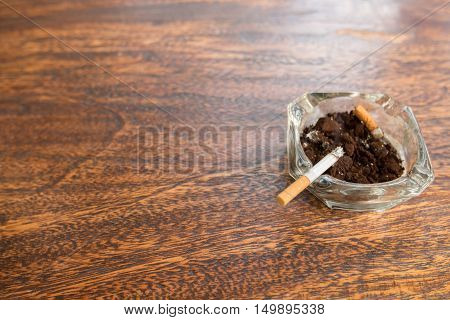 Cigarette butts with ash in ashtray on wooden table with copy space