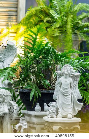 Statue Cupid and waterfall in cozy garden on summer./ Statue of Cupid in cozy garden.