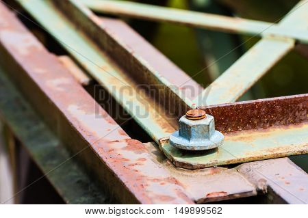 Detail of hexagonal metal screw fastener on corner of partly rusted steel bars and plates.