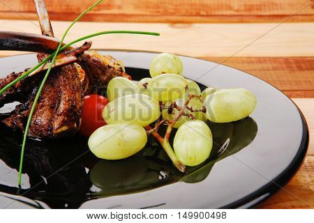 roasted ribs with grapes on wooden table