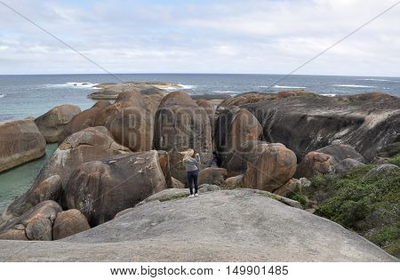 DENMARK,WA,AUSTRALIA-OCTOBER 2,2014: Tourist on massive granite rock formation at Elephant Cove overlooking the Great Southern Ocean in Denmark, Western Australia.
