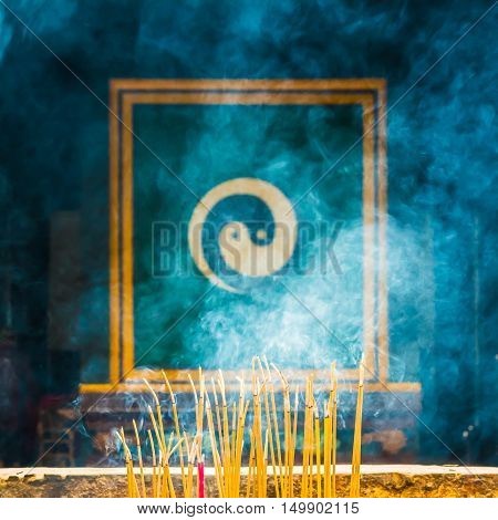 Burning incense with Yin Yang symbol behind the smoke
