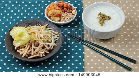 Chinese vegetable festival as rice gruel and fried mixed vegetable served side dish.  (topped roasted pumpkin kernel and mushroom, bean sprouts,cabbage served bean cabbage,sweet radish and pickle )