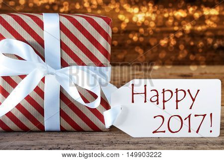 Macro Of Christmas Gift Or Present On Atmospheric Wooden Background. Card For Seasons Greetings, Best Wishes Or Congratulations. White Ribbon With Bow. English Text Happy 2017