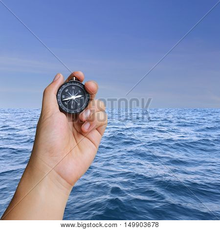 Hand of man holding a compass and view sea in concept of journey at ocean.