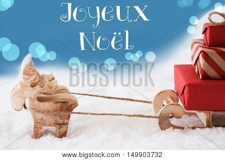 Moose Is Drawing A Sled With Red Gifts Or Presents In Snow. Christmas Card For Seasons Greetings. Light Blue Background With Bokeh Effect. French Text Joyeux Noel Means Merry Christmas