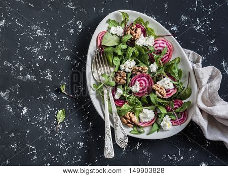 Salad with beets arugula feta cheese and walnuts. On a dark background top view
