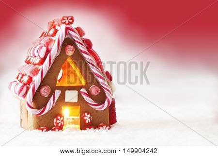 Gingerbread House In Snowy Scenery As Christmas Decoration. Candlelight For Romantic Atmosphere. Red Background With Snow. Copy Space For Advertisement