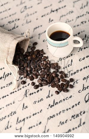 Heap coffe beans and cup of fresh coffee on decorative napkin