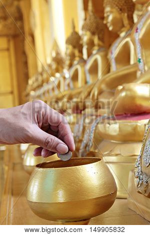 Give coin in alms bowl, a man put a Baht coin in a monk bowl for making merit or donation, buddhism Thai people donating money for temple, row of bowl