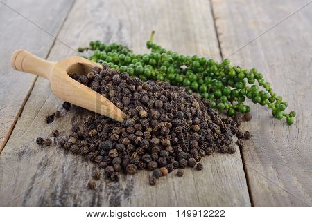 fresh green peppercorns and dry black pepper on wooden table