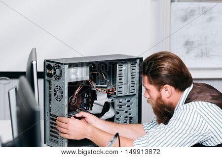 Bearded repairman disassembling computer unit. Separating motherboard out of CPU in electronic repair shop