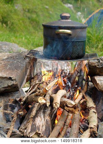 soup in a pot at fire place Summer trekking activity