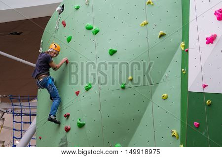 Moscow, Russia - August 30, 2016. The Teen on climbing wall in shopping complex Zelenopark