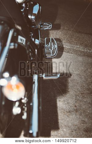 Close-up of motorbike side with throttle pedal against asphalt ground