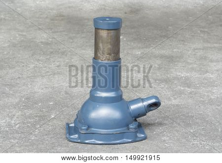 Old and dirty hydraulic bottle jack on concrete floor