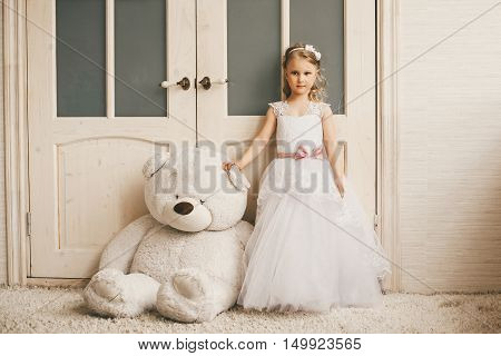 Little princess like a bride standing with a big plush toy