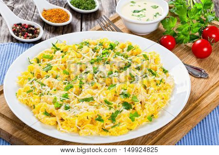 Fettuccine Alfredo served in a sauce of cream butter and grated Parmesan cheese sprinkled with parsley on white dish on old planks