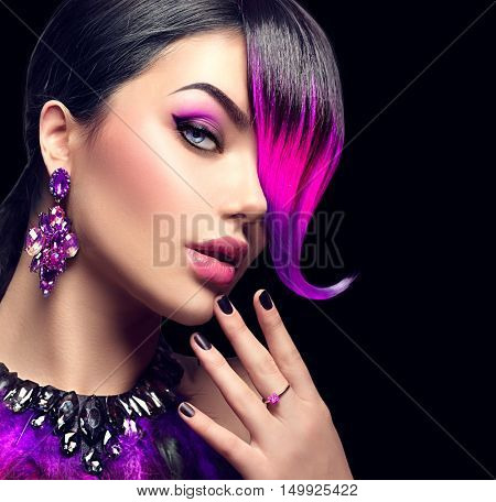 Sexy Beautiful fashion woman with purple dyed hair fringe hairstyle and violet color accessories, necklace and earrings with crystals. Beauty model girl portrait isolated on black background.