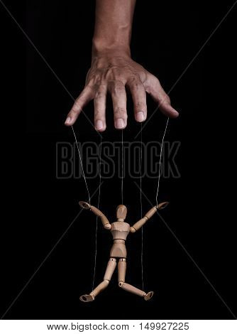 Hand controlling wooden puppet marionette, low key images, on black background