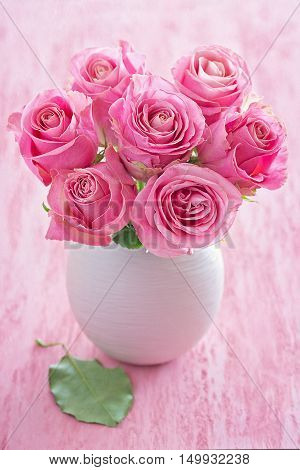Beautiful fresh roses flowers in a vase on a pink background.