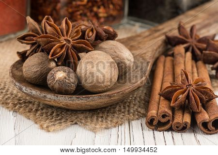 Nutmeg and star anise in the wooden spoon on old wooden table. Selective focus.