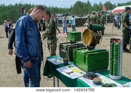 Tyumen, Russia - June 11, 2016: Race of Heroes project on the ground of the highest military and engineering school. Exhibition of weapon. Man - visitor of show examines samples at stand with mines