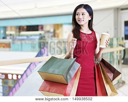 young beautiful asian woman female shopper carrying colorful paper bags and a cup of coffee walking in shopping mall