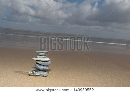 Zen stone in the sand. Background on the sea